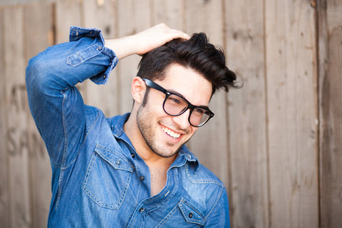 smiling man in denim shirt with hand in his hair