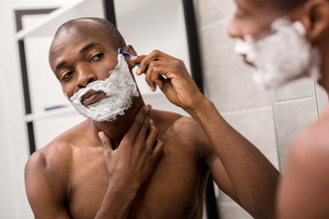 man shaving his face in the mirror