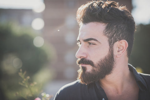 Side profile of bearded man outdoors in city