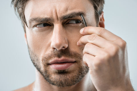 man using tweezers to groom his eyebrows