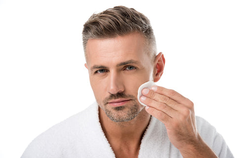 man in white robe applying product to oily skin with cotton pad
