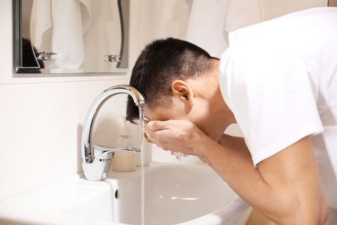 man washing his face to prevent oily skin