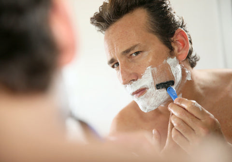 man using a mirror to shave his face