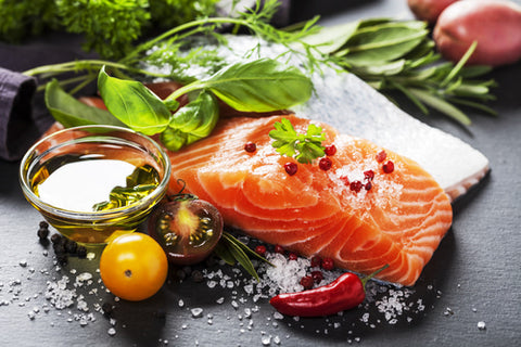 raw salmon, olive oil, tomatoes, and other healthy foods on prep board