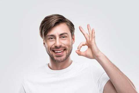 "man in white t-shirt smiling widely while displaying the ""okay"" gesture with one hand"