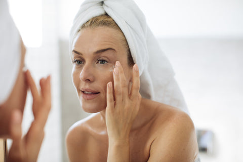 woman with hair wrapped in a towel applying eye cream in a mirror
