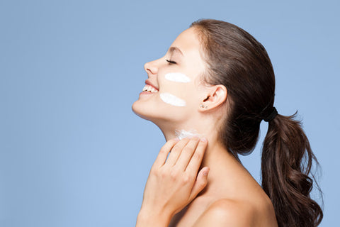 side profile of woman with swipes of moisturizer on her face and neck