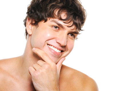 smiling man with shaved face touching his chin