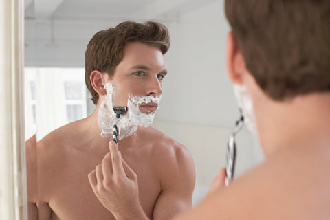 reflection of man shaving the side of his face