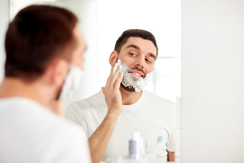 man smiling while applying shaving cream to his face in a mirror