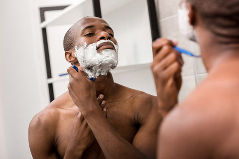 reflection of man shaving his neck area in a mirror and implementing shaving tips