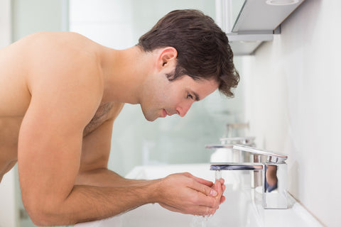 man leaning over a sink and filling his hands with water