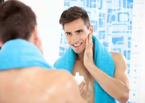 man with towel around his neck applying aftershave to his face