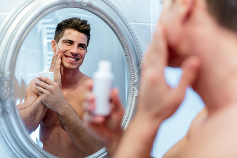 man looking in mirror while applying product to his face