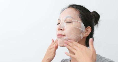 woman applying a sheet mask to her face to receive sheet mask benefits