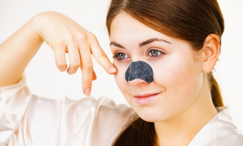 Woman applying pore strip to help unclog pores