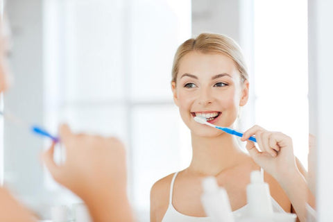 woman in a bathroom using a toothbrush to get soft lips