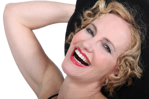 woman with blonde hair and red lips laughing with her head thrown back