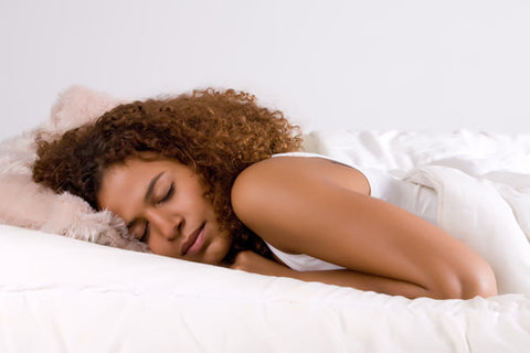 woman sleeping on her stomach with arms folded underneath her body