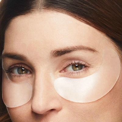 close up of woman wearing SiO Beauty patches under her eyes