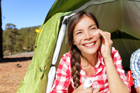 woman applying sunscreen to her face while camping outdoors