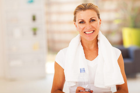 woman at health club smiling and holding bottle of water