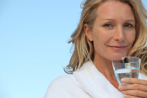 woman drinking water to achieve youthful skin