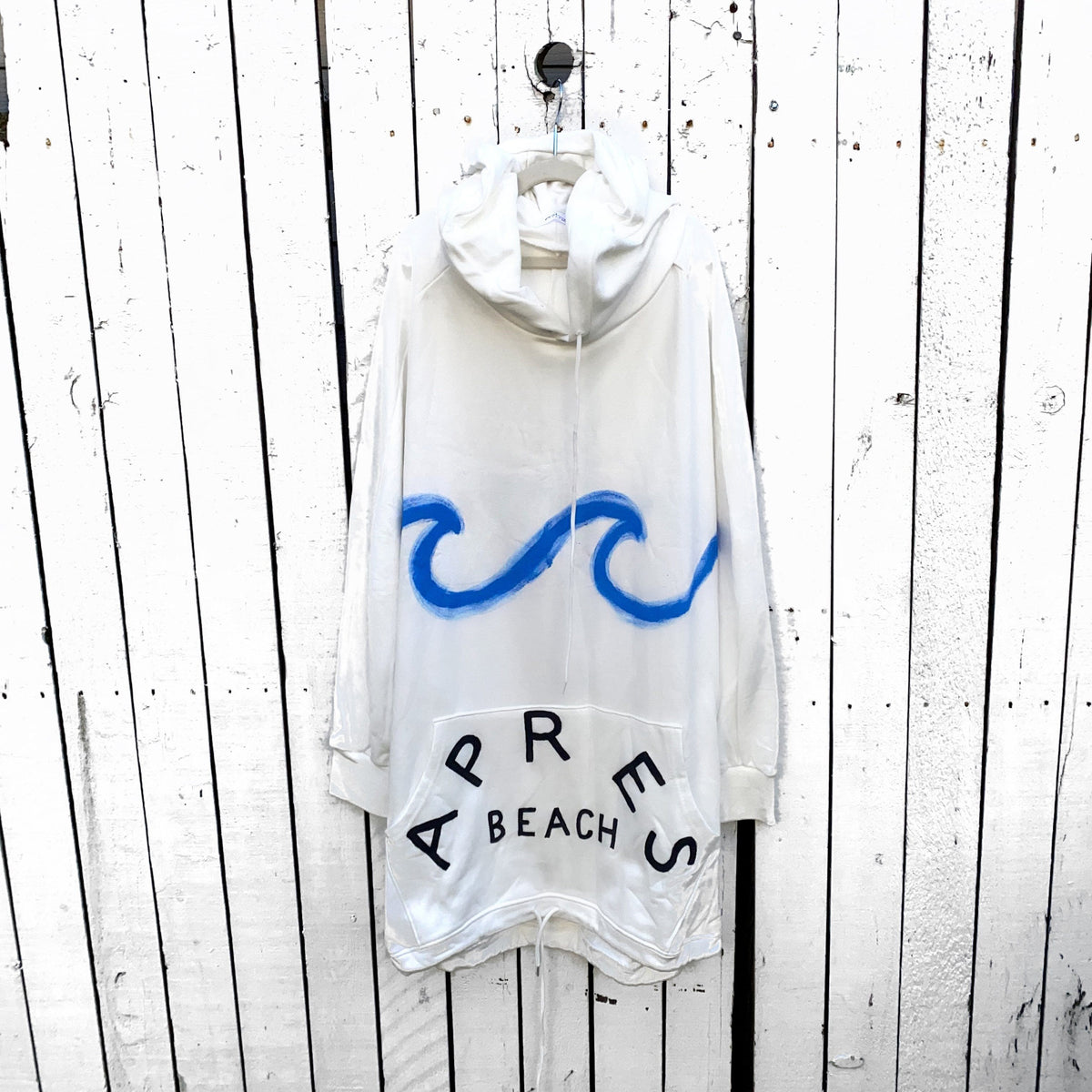 Oversized white sweatshirt dress. Blue wave painted along entire sweatshirt, on chest area, with APRES BEACH painted in black on front pocket. Signed @wrenandglory.