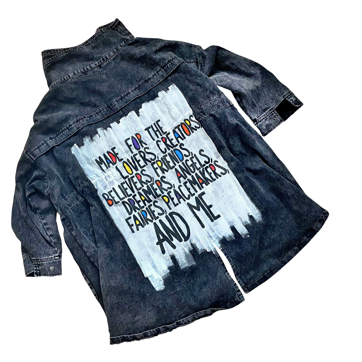 Asymmetric, oversized black denim jacket. Wording on back 'Made for the lovers, creators, delivers, friends, dreamers, beauties, angels, fairies, peacemakers, artists, heartbreakers and me', over white base, with randoms pops of color. Signed @wrenandglory.