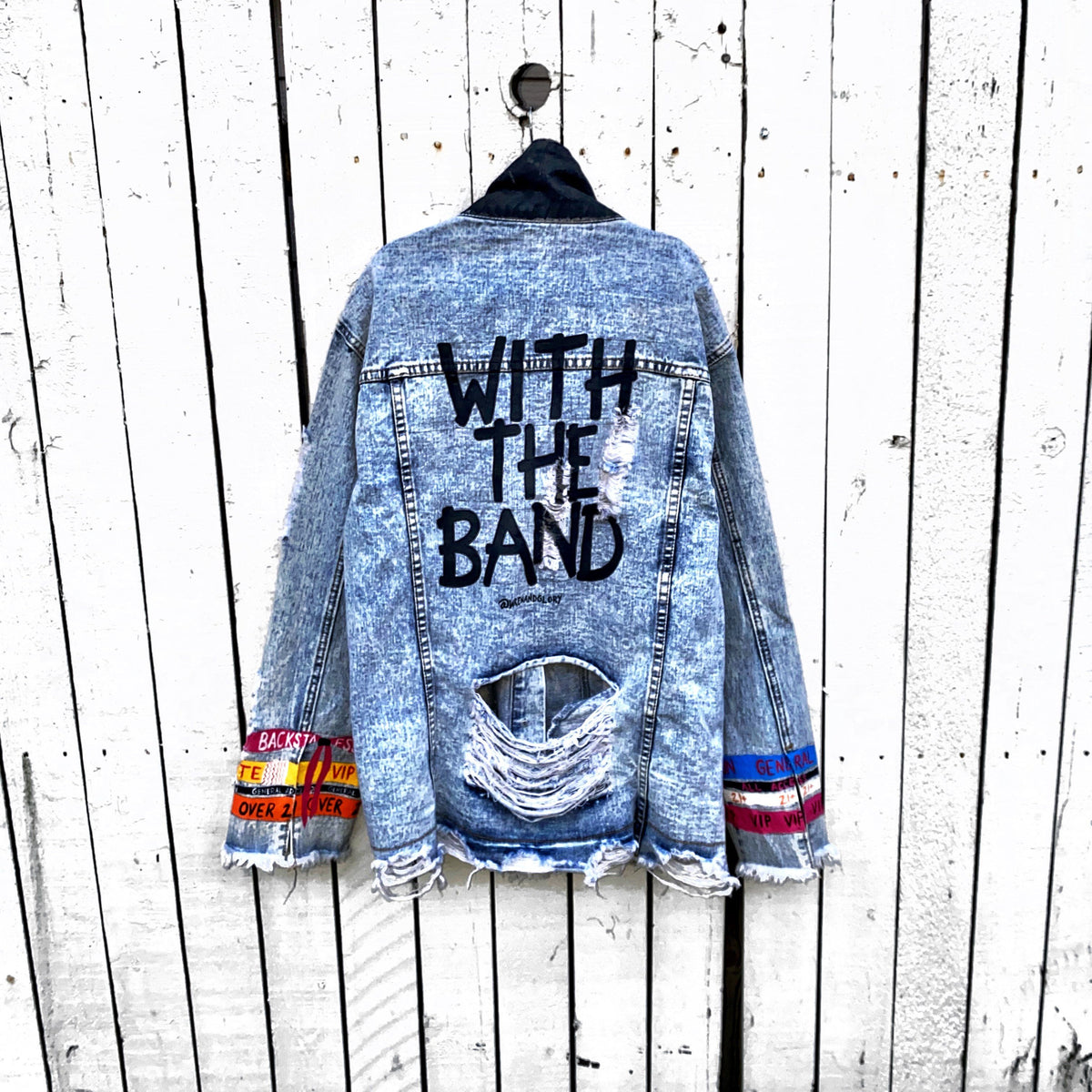 Medium blue denim wash. Festival bracelets painted up the sleeves on each side of jacket, with 'WITH THE BAND' painted in black on back.  Front pockets and collar painted black. Signed @wrenandglory.