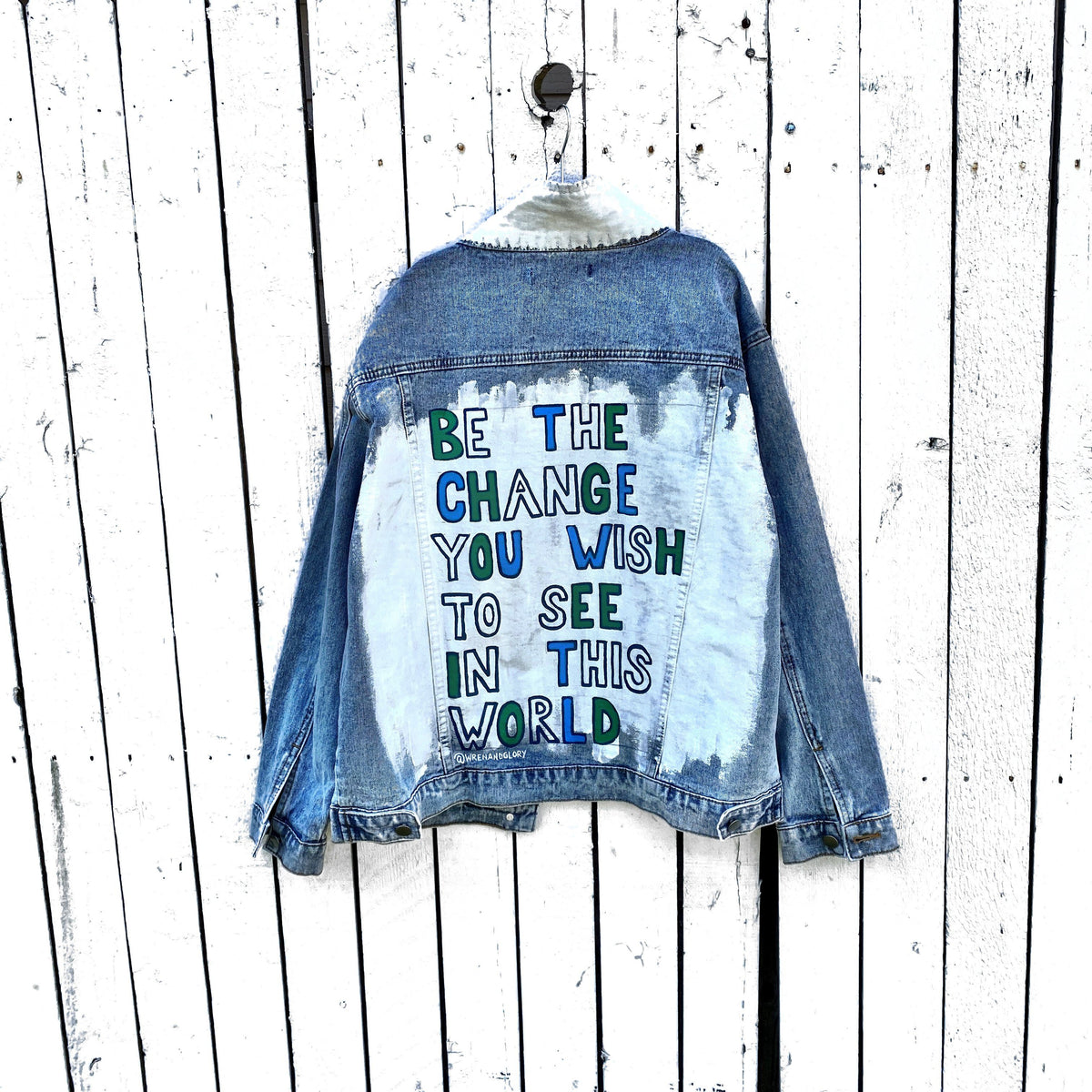 Lighter blue denim wash. White base on back, with BE THE CHANGE YOU WISH TO SEE IN THIS WORLD painted on the back in blues & green, in block letters. Collar and front pockets painted white. 12 Earth Day / environment friendly related pins on the front. Signed @wrenandglory.