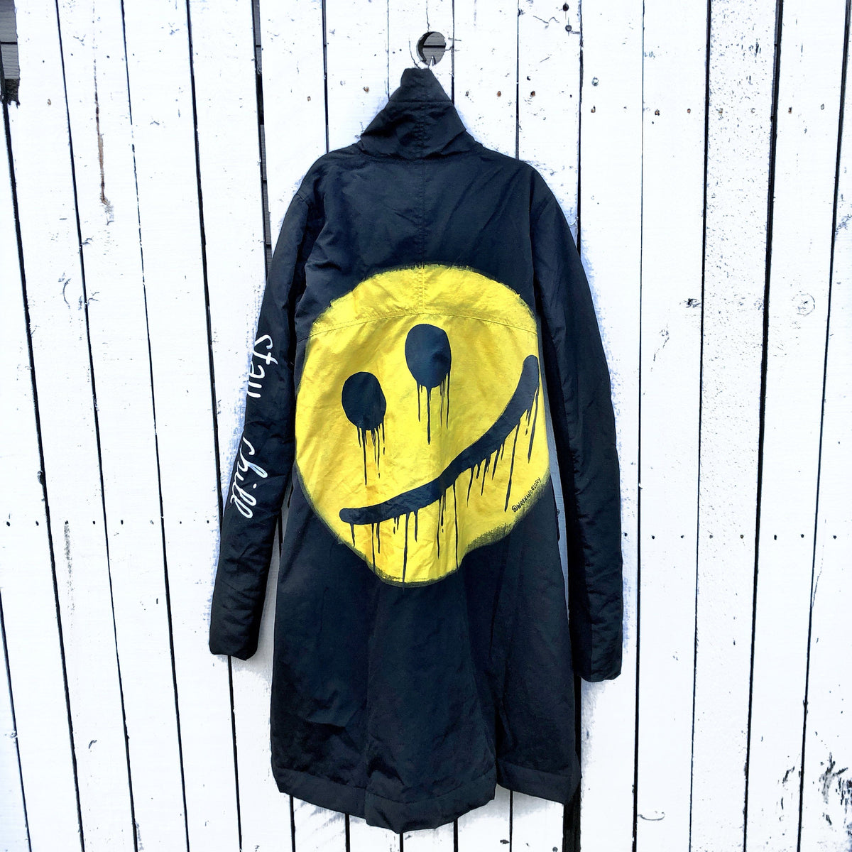 The COOLEST puffer jacket. Large smiley painted on back in yellow, with black drip eyes and mouth. STAY CHILL painted in white on sleeve. Signed @wrenandglory.