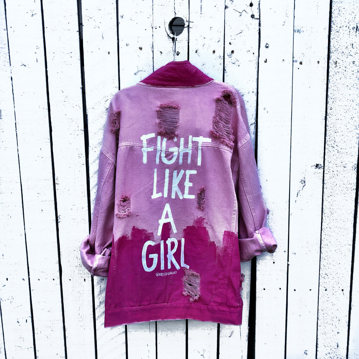 Pink /blush colored denim. Hot pink painted along the bottom half of the jacket, with FIGHT LIKE A GIRL painted in white on back. Small Breast Cancer Awareness ribbon painted on front upper pocket. Signed @wrenandglory.