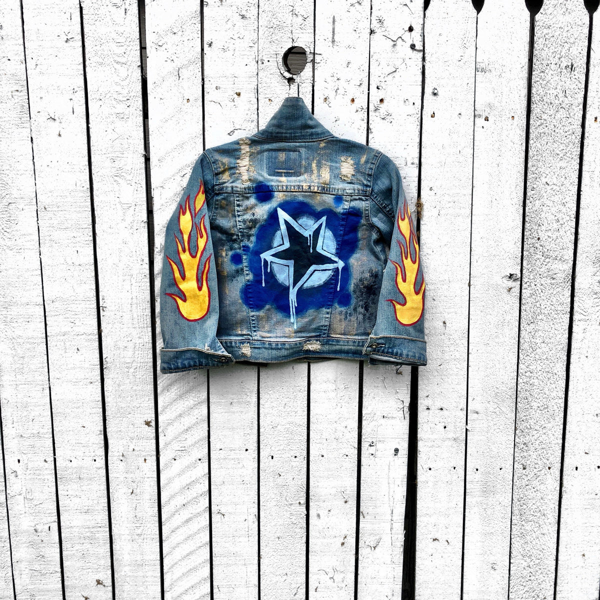Blue denim jacket. Hand painted design, with stars, flames, and metallics.  Childs name available on front, left corner. Each jacket wrapped in a silk wrap bracelet with a child's charm. Each piece signed @wrenandglory.