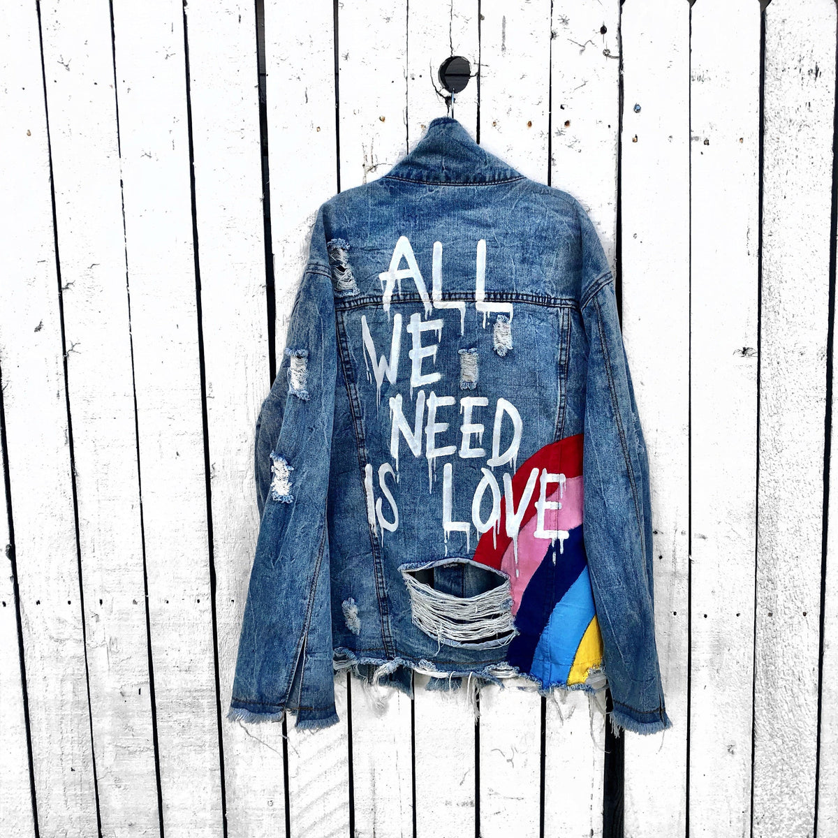 Medium blue denim wash. Large rainbow, spreading across the back to the front, with 'All We Need Is Love' painted in white with a dripping effect. Signed @wrenandglory.