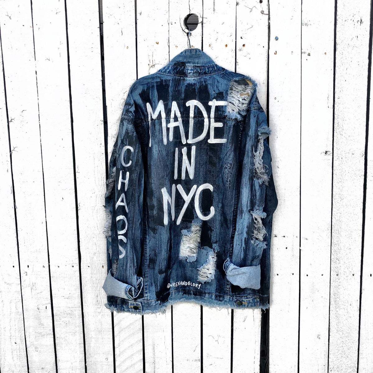 "Medium blue denim wash. Black base all over, with 'MADE IN NYC' painted on back in white. CHAOS painted down the arm in white. Assorted 1"" pins on bottom left, bottom pocket area. Signed @wrenandglory."