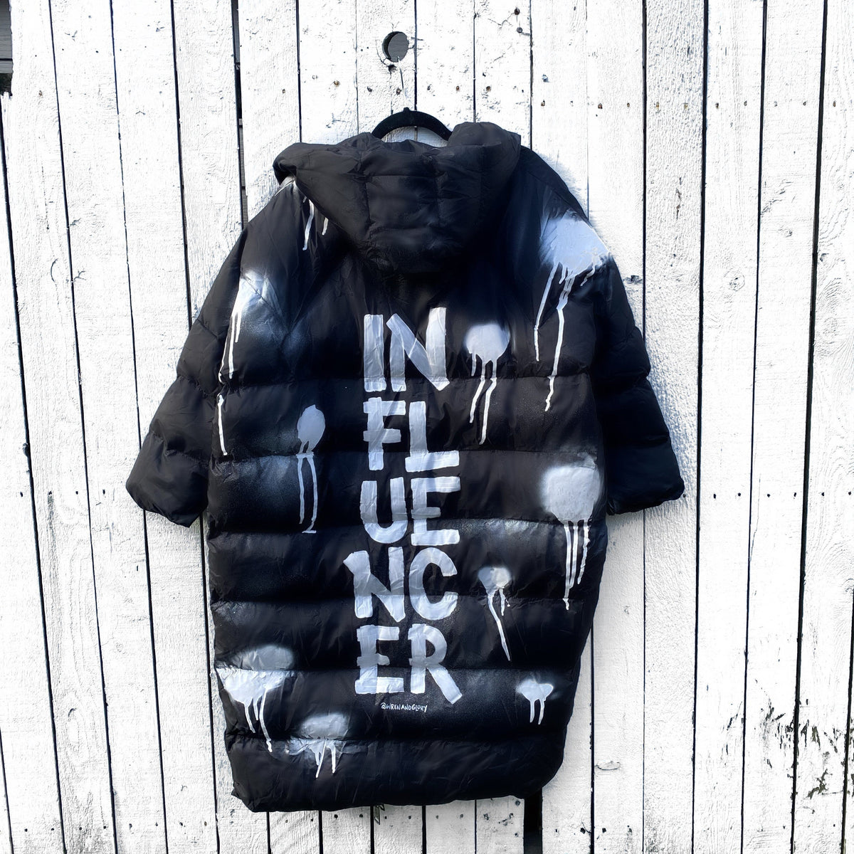 The COOLEST, MOST COMFORTABLE puffer jacket. White spray paint surrounding entire jacket, with INFLUENCER painted down the back, center, in large text. Signed @wrenandglory.