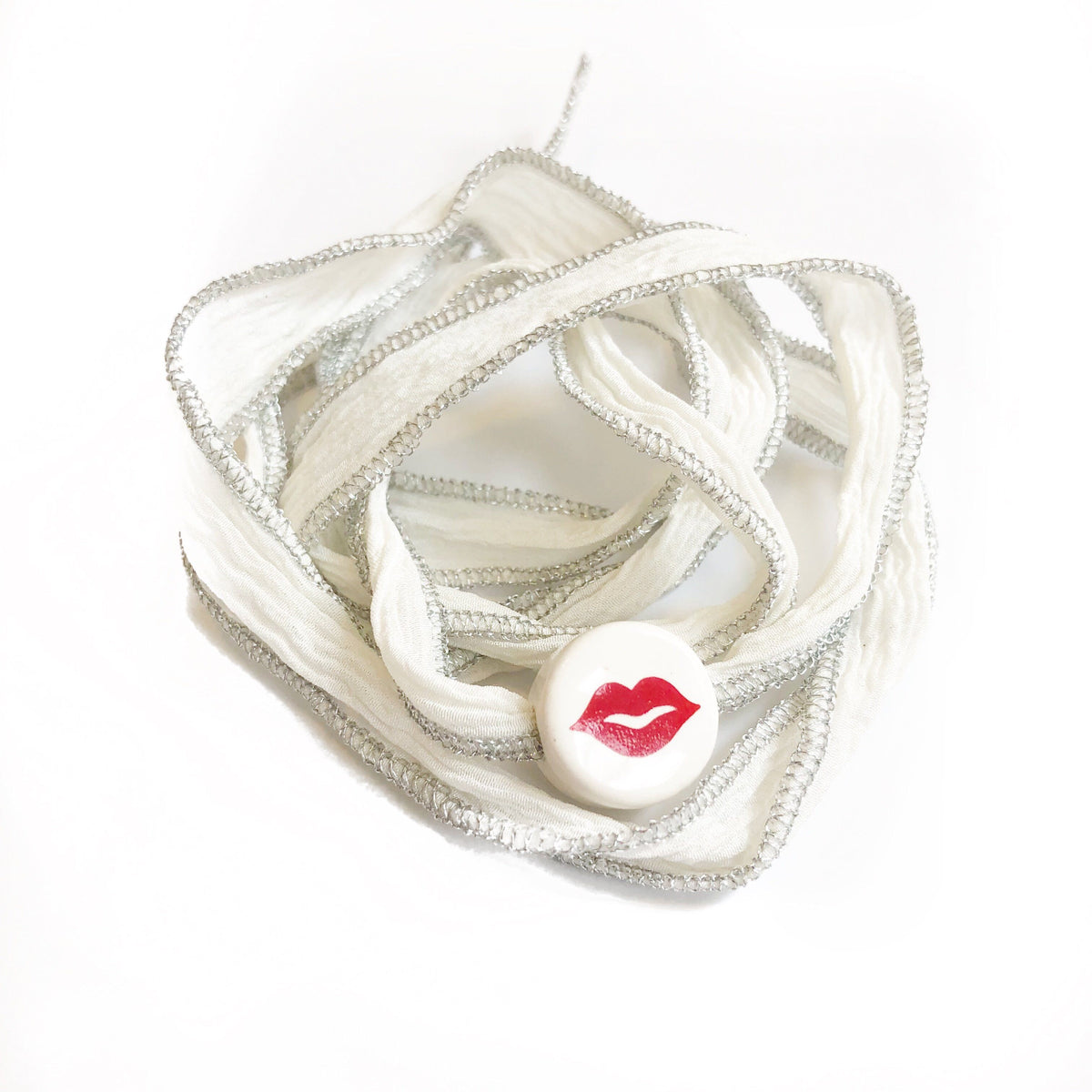White metallic silk wrap with lips charm. Silk wrap hand made, and hand dyed.