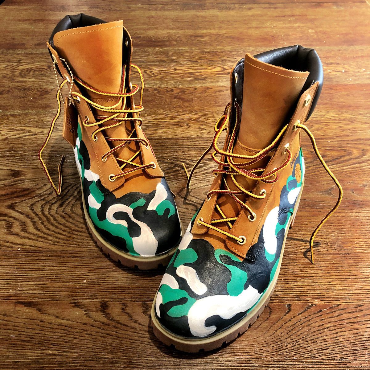 Green, white and black camo style painted boots. Painted on waterproof Timberland Boots. Signed @wrenandglory.