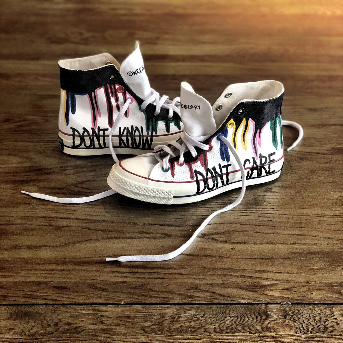 Black and rainbow colored white, canvas sneakers. DONT KNOW painted on one, DONT CARE painted on other. Painted on Converse high tops, Chuck Taylor All Star '70 High.