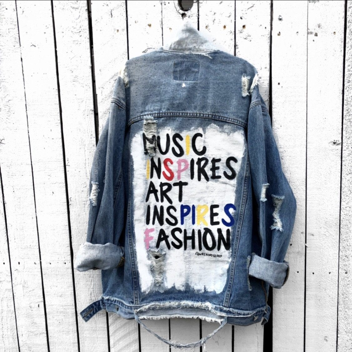 "Medium blue denim wash. White base on back, with 'Music Inspire Art Inspires Fashion' in black and other assorted colors. Color and front pockets painted white. Assorted 1"" pins on bottom left, front pocket area. Signed @wrenandglory."