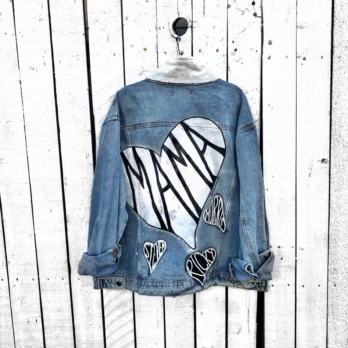 Lighter blue denim wash. Large white heart on back with MAMA painted inside in black. Smaller black hearts surrounding the larger one, customized with kids names. Collar and front pockets painted white. Signed @wrenandglory.