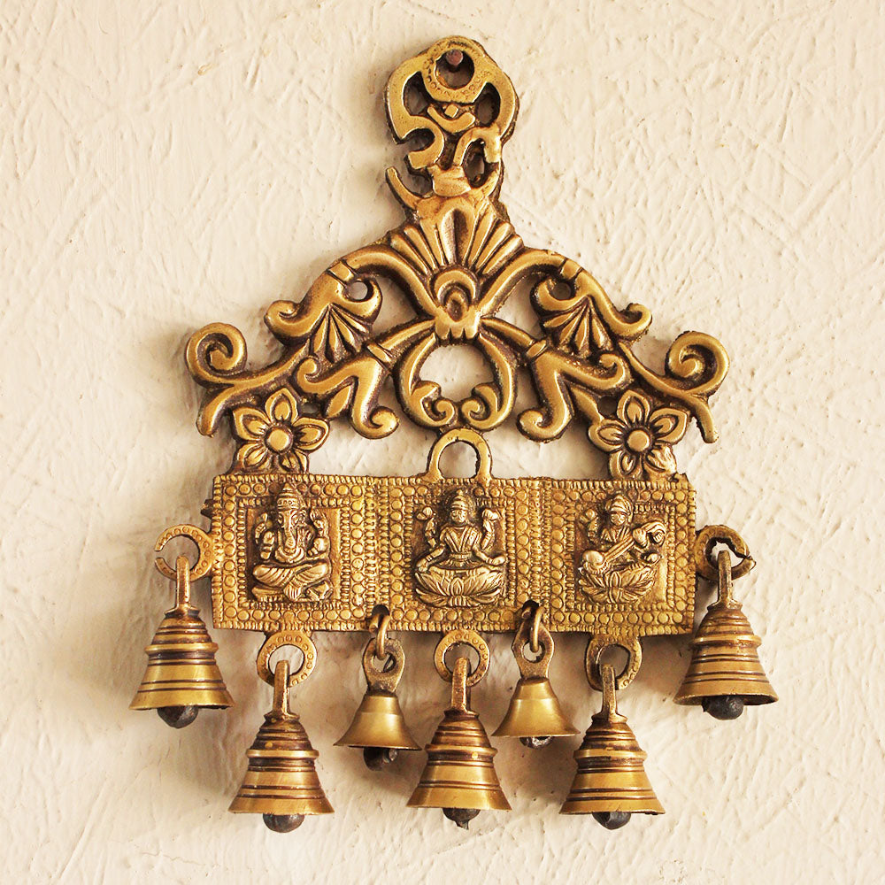 Wall Hanging of Hindu Gods Ganesha, Lakshmi & Saraswati with 7 Bells Crafted In Brass - H 24 cm x W 18 cm - theindianweave