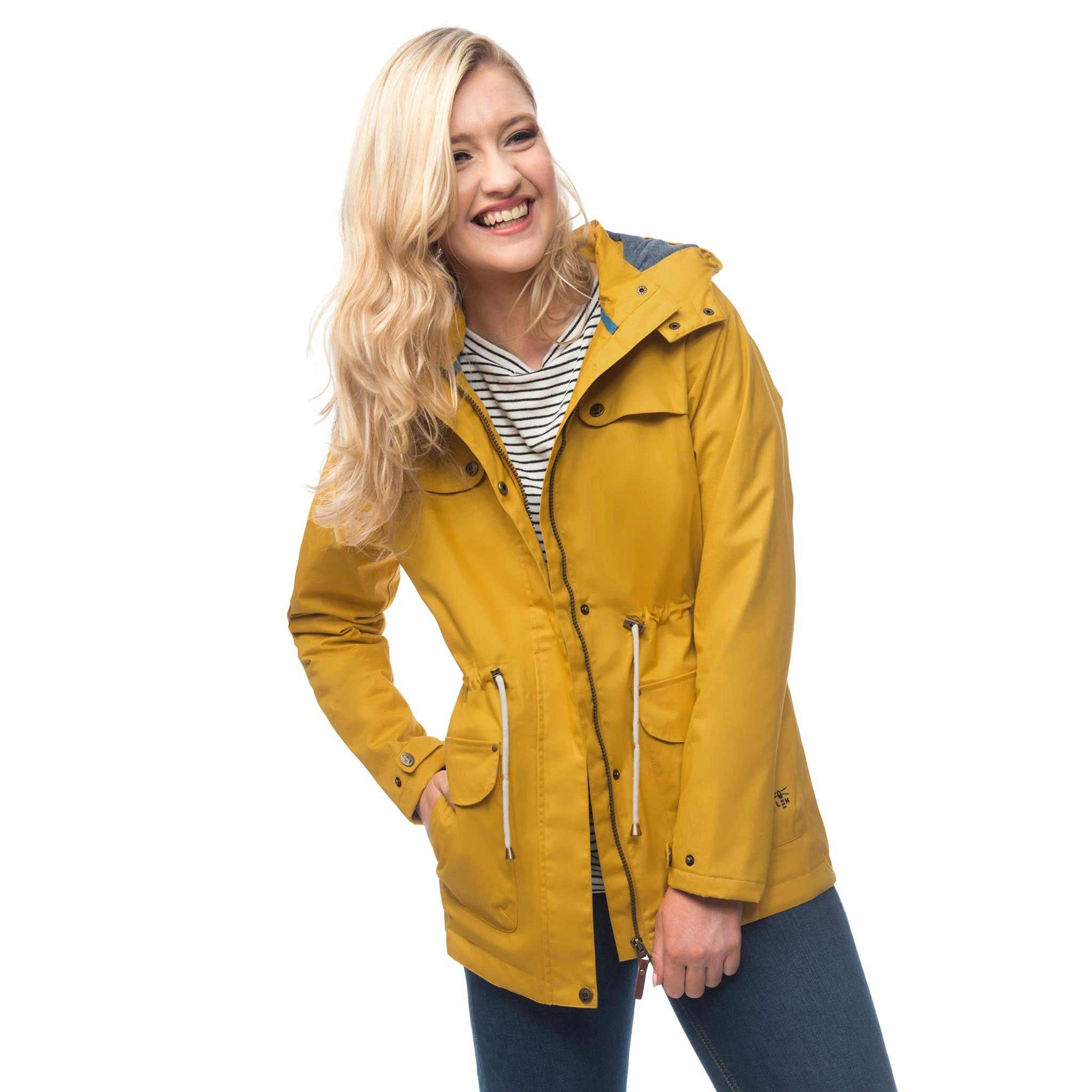 Lighthouse Womens Lana Waterproof Hooded Raincoat in Yellow. Coat unzipped. Hands in pockets.