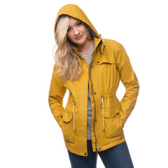 Lighthouse Womens Lana Waterproof Hooded Raincoat in Yellow. Coat unzipped. Hood up. Hands in pockets.