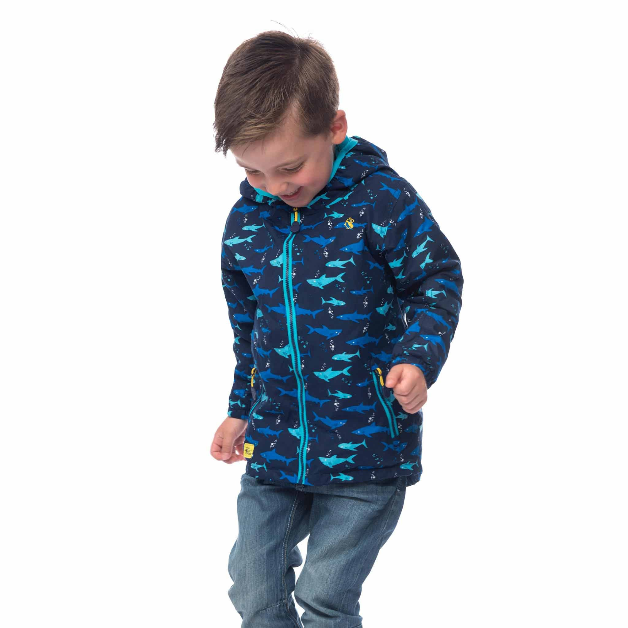 Lighthouse Boys' Ollie Fleece Lined Waterproof Hooded Raincoat in Navy with Shark Print. Fully Zipped.