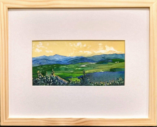 """Across the Valleys"" is a 4.5 x 9 inch watercolor and ink painting on paper by Rebecca M. Fullerton, depicting the view from Mount Hunger over the hills and valleys of Vermont all the way to Camel's Hump in the distance. The sky is a golden yellow of sunset hues while the land below is painted in greens and blues.  This view shows the painting in its frame."