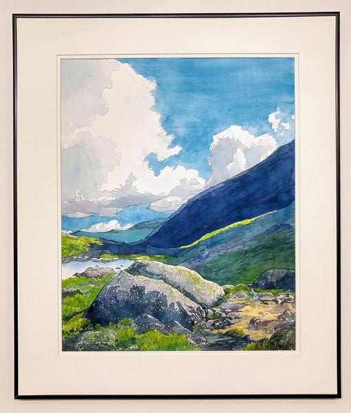 """Alpine Light"" is a 16 by 20 inch watercolor and ink painting on paper by Rebecca M. Fullerton, depicting Star Lake, the slopes of Mount Adams, and glimpses of the Presidential Range in the White Mountain National Forest of New Hampshire. Huge white clouds move over blue mountains, green alpine plants and craggy granite boulders on the edge of a mountain pond. This view shows the painting in its frame."