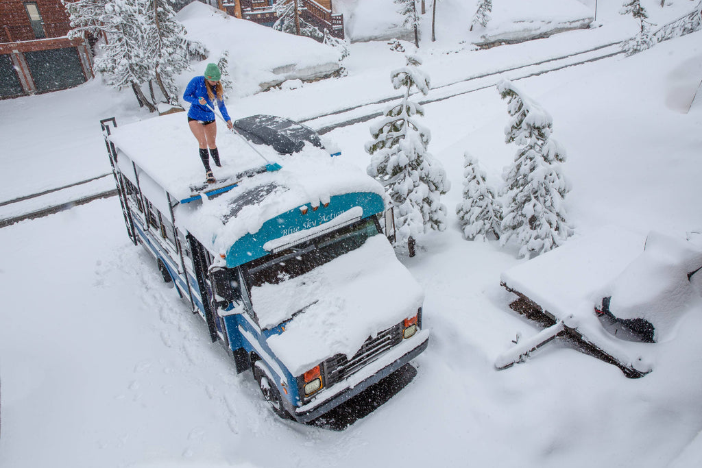 Blue bus adventure shoveling snow off the roof