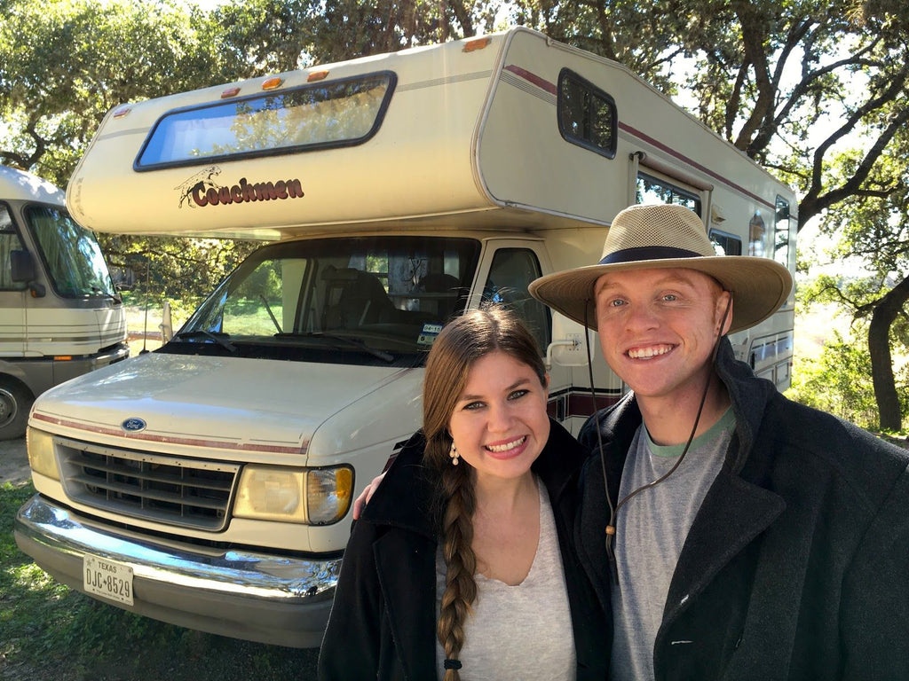 Heath and Alyssa standing in front of their old RV, living Full-time in RV